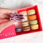 Multi-coloured Nadège macarons. A purple macaron with a bite taken out of it is held closer to the front of the image.