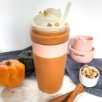 Pumpkin smootie with whipped cream in small blender. Props include blender lid, two small gourds, cinnamon sticks, walnuts, a white straw and a blue napkin.
