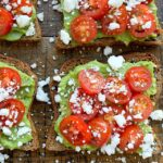 Four pieces of avocado toast on a wood backdrop with tomatoes and crumbled feta