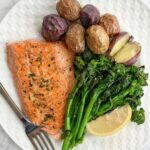 Pan-fried salmon, rapini, mini baked potatoes and a lemon wedge on a white plate with a stainless steel fork on the bottom left corner of the plate