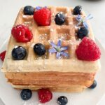 Stack of waffles with blueberries, raspberries, purple flowers and powdered sugar on a white plate.