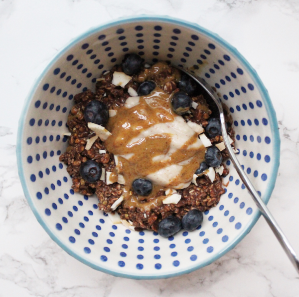 Chocolate oats in a blue patterned bowl with a marble backdrop, with yogurt, blueberries. coconut and peanut butter drizzled on top. Stainless steel spoon scooping the oats.