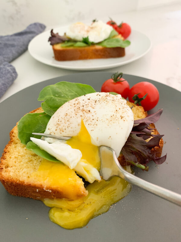 Cornbread with a poached egg and lettuce on top with a fork breaking the yolk on a blue plate. Another piece of cornbread with an egg on it is in the background.