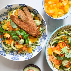 Two tempeh bowls with zucchini, shredded carrots, sliced yellow pepper, avocado and basil. Props include small bowl with yellow bell pepper to the top right, and half of an avocado to the bottom.