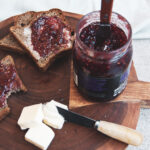 Wood plank with three pieces of buttered toast with jam. One piece with a bite taken out of it. A jar of jam with a knife in it and three cubes of butter with a small knife in one.