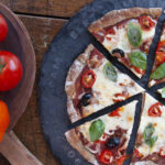 Pizza with tomatoes, black olives, basil, tomato sauce and cheese, sliced on a round stone platter. Bowl of tomatoes to the left of the pizza.
