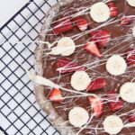 Nutella, strawberry, banana and white chocolate pizza on a black wire rack on a white counter.