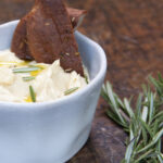 Hummus in a small blue bowl, with two pieces of bread, oil and rosemary on top of a wood surface with a few sprigs of rosemary