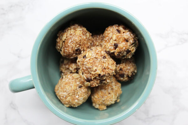 """Oatmeal """"cookie"""" energy balls with chocolate chips in a large blue mug."""