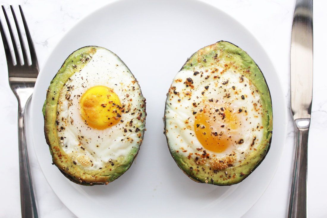 Two baked avocado halves with eggs and pepper on a white plate with a fork to the left and a knife to the right.