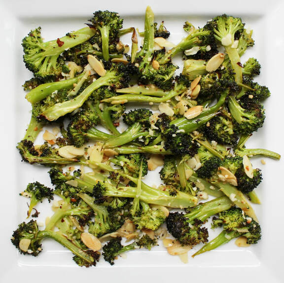 Lemon Broccoli with almonds and parmesan on white plate