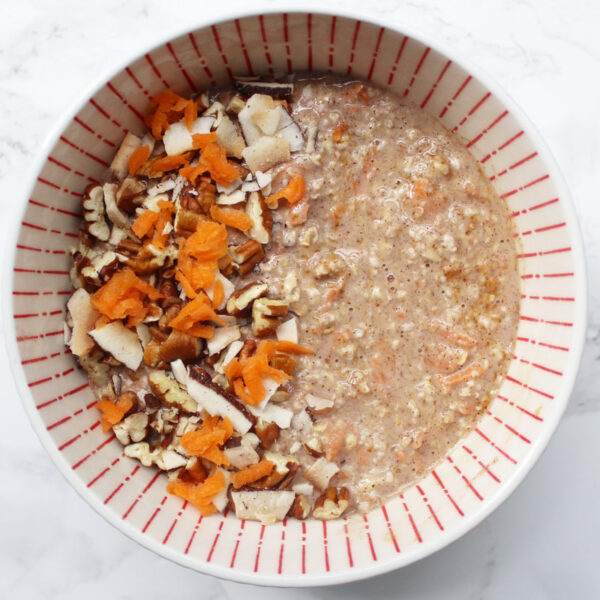 Carrot Cake Overnight Oats in a white and orange bowl. carrot, pecans and coconut on top.