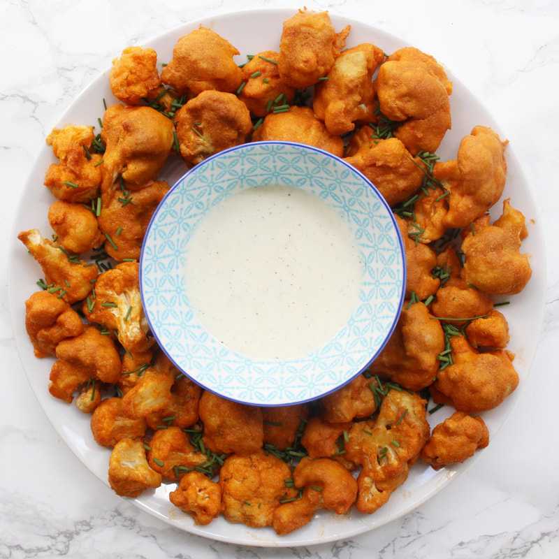 Spicy baked cauliflower wings on a round white plate with ranch dip in a blue patterned bowl in the middle