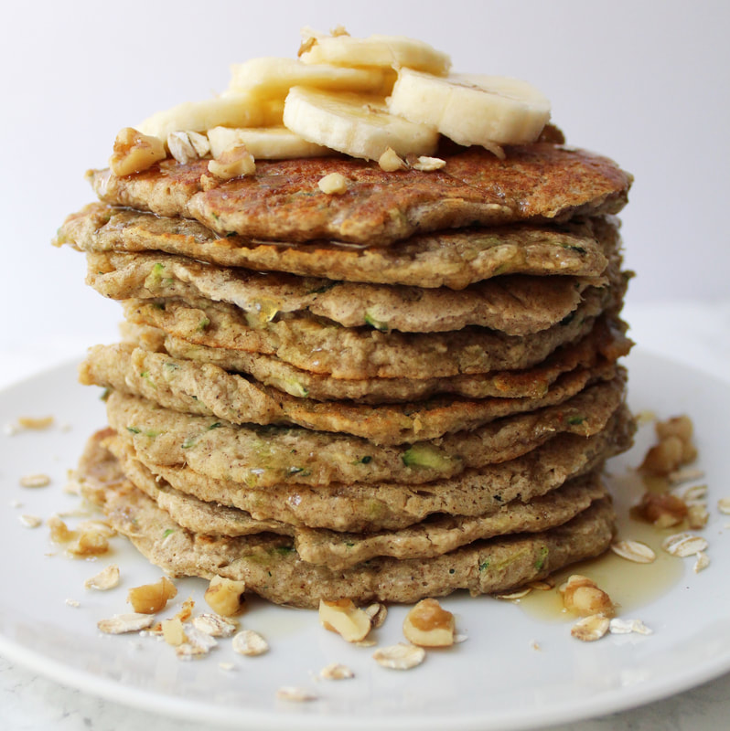 Stack of Banana Zucchini Pancakes with oats, walnuts, sliced bananas and syrup on top.