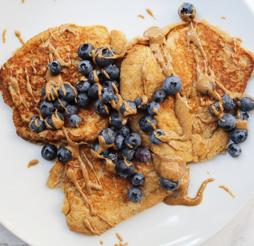 Three banana pancakes on a white plate, with blueberries and drizzled with peanut butter.