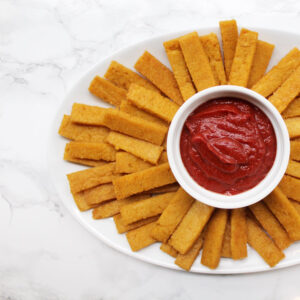 Baked polenta fries on a white plate with ketchup in the middle.