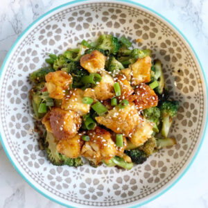 Tofu broccoli bowl with sesame seeds and green onions in a patterned bowl on a marble backdrop.