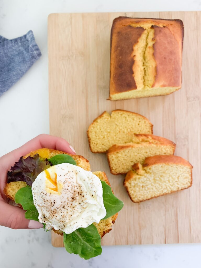 Hand holding slice of cornbread with lettuce, poached egg and pepper. Sliced cornbread on wooden cutting board in the background.
