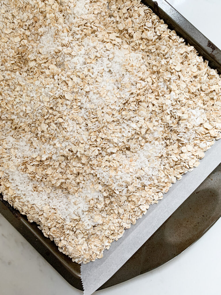 Oats and shredded coconut on a baking sheet with parchment.