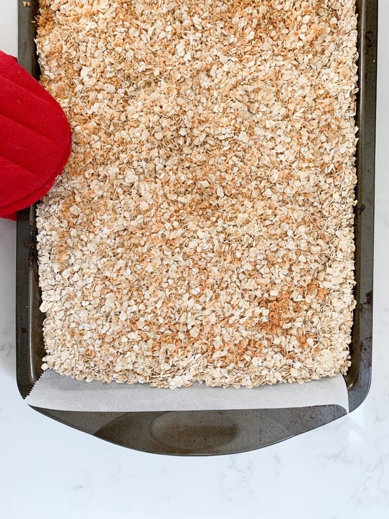 Toasted oats and shredded coconut on a baking sheet with parchment and a red oven mitt holding the sheet.