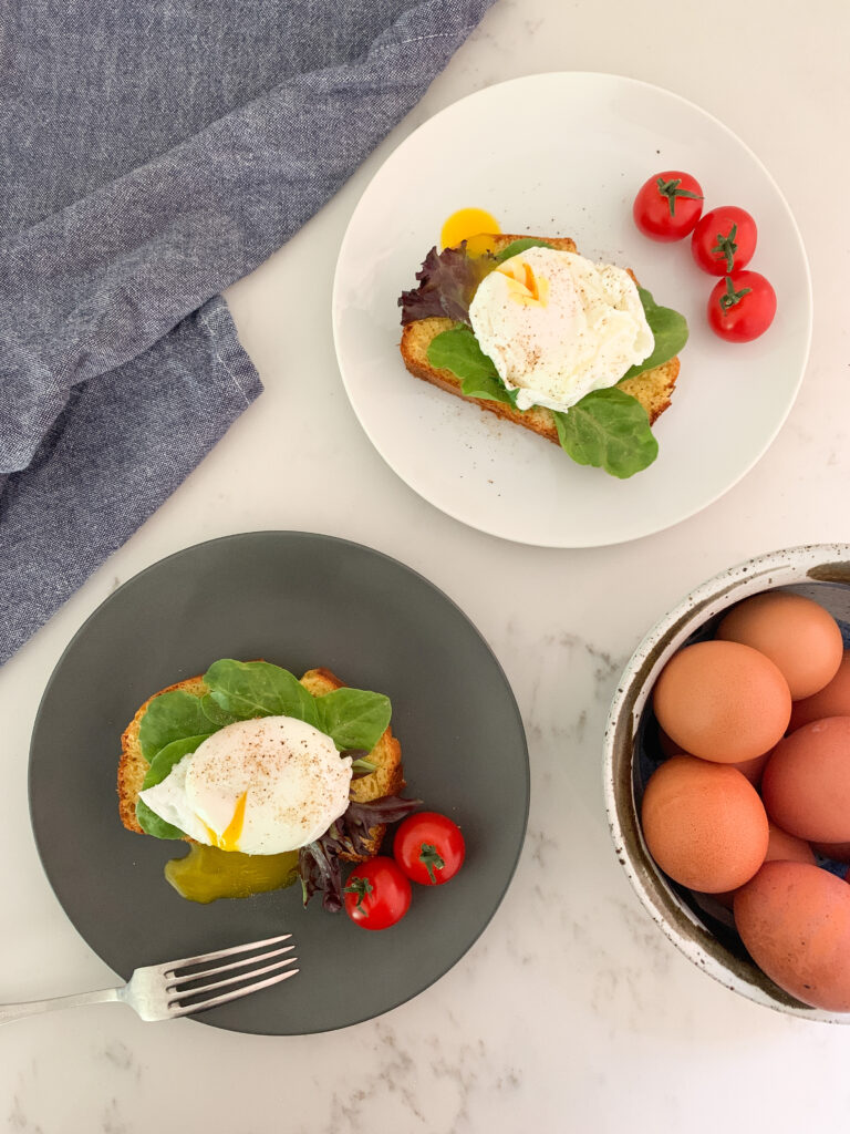 Two plates, each with slice of cornbread, lettuce, poached egg, pepper and side tomatoes. Blue napkin in the top left corner and a bowl of whole eggs in bottom left corner.