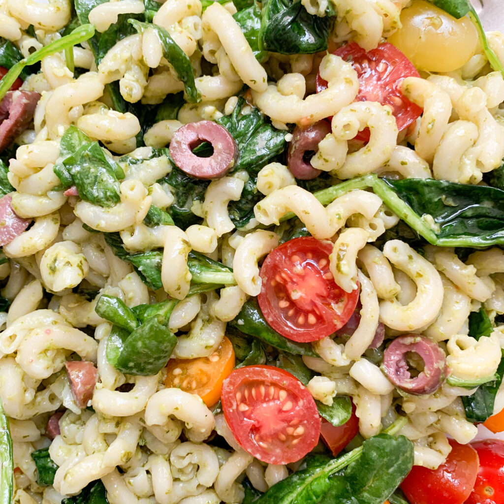 Close-up of pesto pasta salad with brown rice pasta, pesto, spinach, tomatoes and olives.