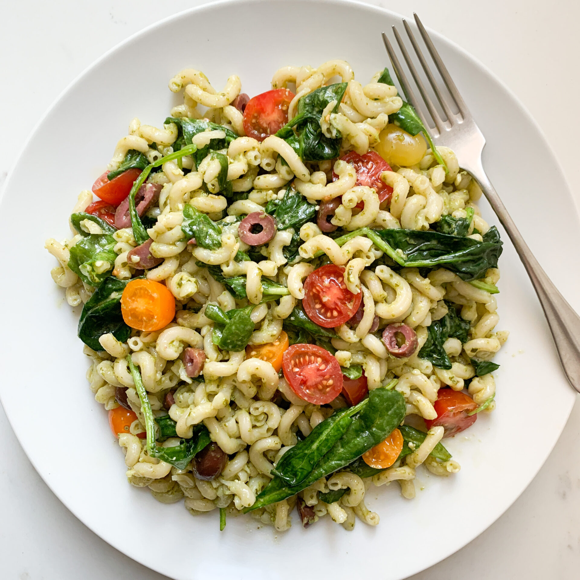 White plate filled with pasta salad - including brown rice pasta, pesto, spinach, tomatoes and black olives - with a fork on the top right.