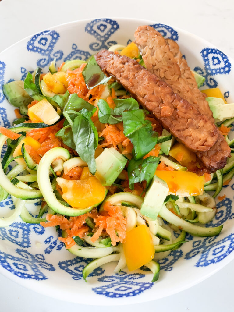 Close-up of bowl with zucchini, carrots, pepper, herbs and tempeh.