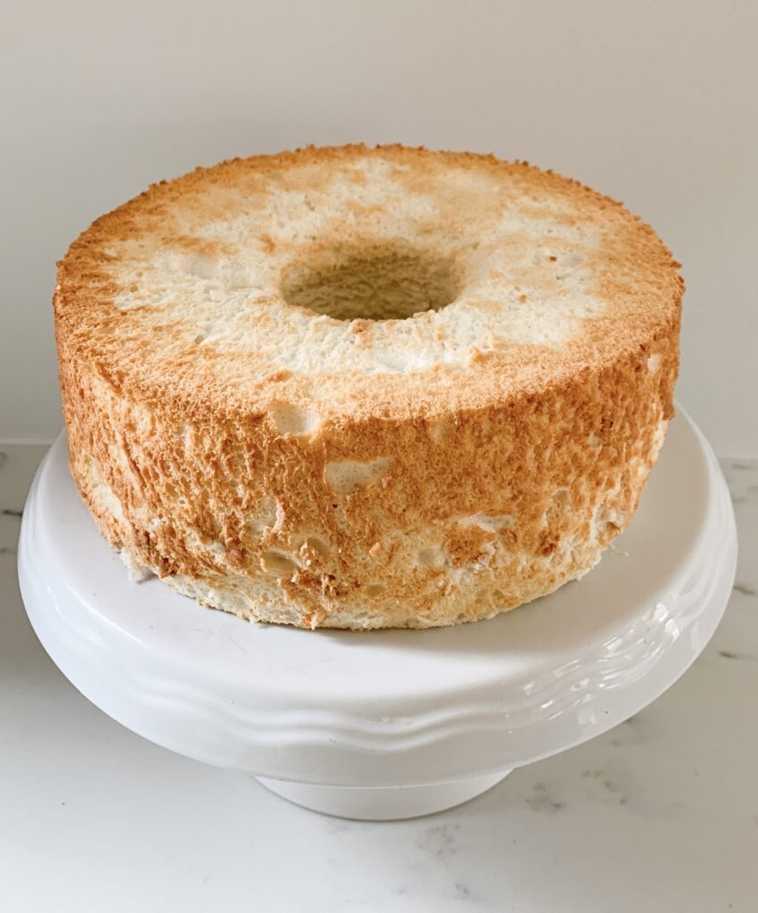 Plain angel food cake on white cake stand.