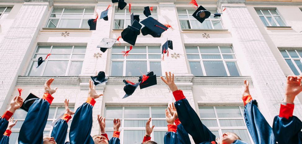 Group of kids jumping in the air throwing their graduation caps