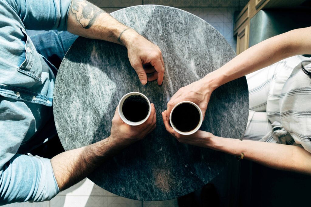 Two people sitting at round table with coffee