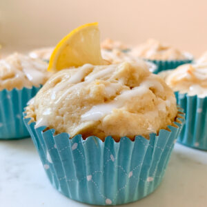 Lemon muffin with glaze in blue muffin cup. Lemon slice on top and other muffins behind.