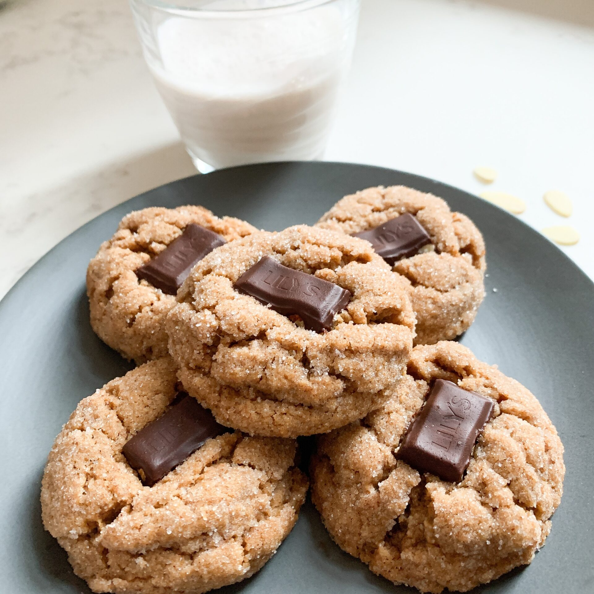 Cookies with chocolate in middle on blue plate with glass of milk.